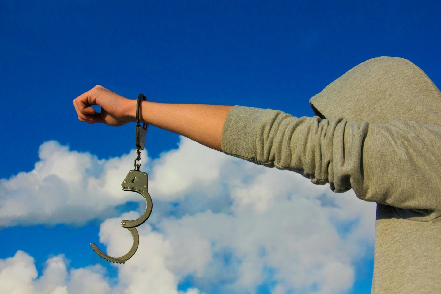 Person with handcuffs with sky background