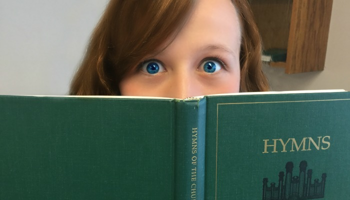Girl looking scared over hymnal pages